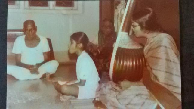 Little Nanditha singing, with grandmother Smt Thulasi Ammal on the violin and mother Smt Ravi Ravi on the tambura. Grandfather Shri M.R. Subramaniam listens in rapt attention.
