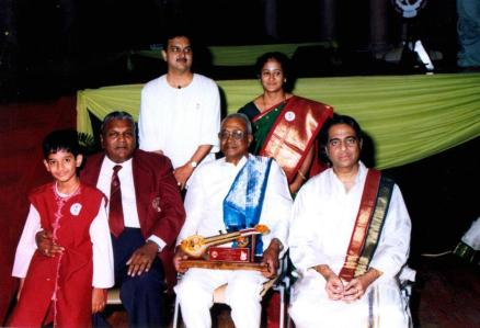 During his concert tour of South Africa, Sathya sits on the lap of Dr T.P. Naidoo, Chairman, Indian Academy, Durban. Also in the picture are Sathya's parents and Sangita Kalanidhi Madurai Shri T.N. Seshagopalan