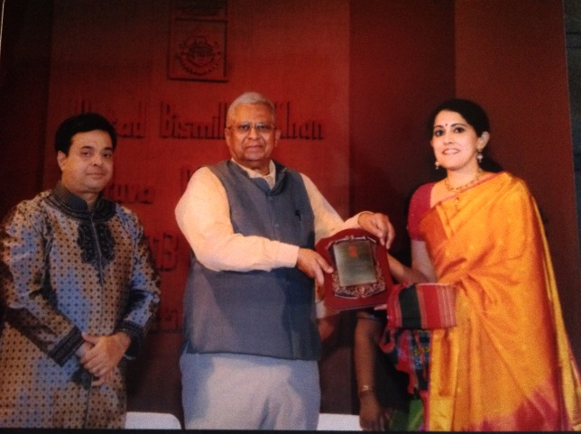 Amritha receiving the prestigious Ustad Bismillah Khan Yuva Puraskar from the Governor of Tripura, Shri Tathagata Roy. The Chairman of the Sangeet Natak Akademi, Shri Shekhar Sen, looks on.